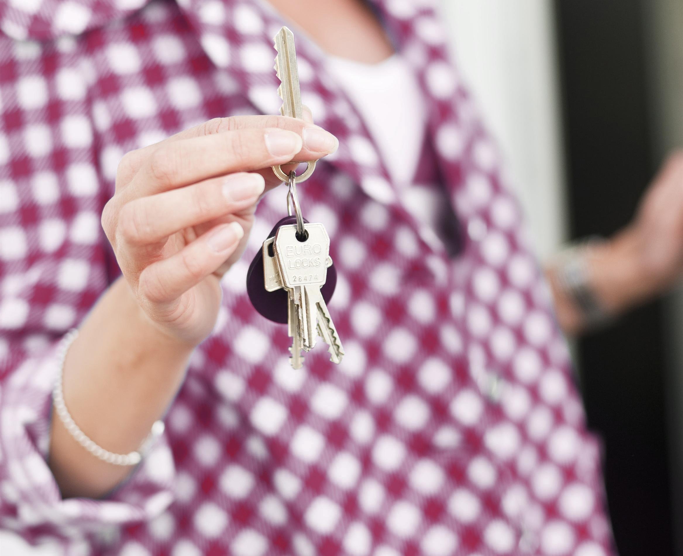 Kvinna håller nyckelknippa i handen.