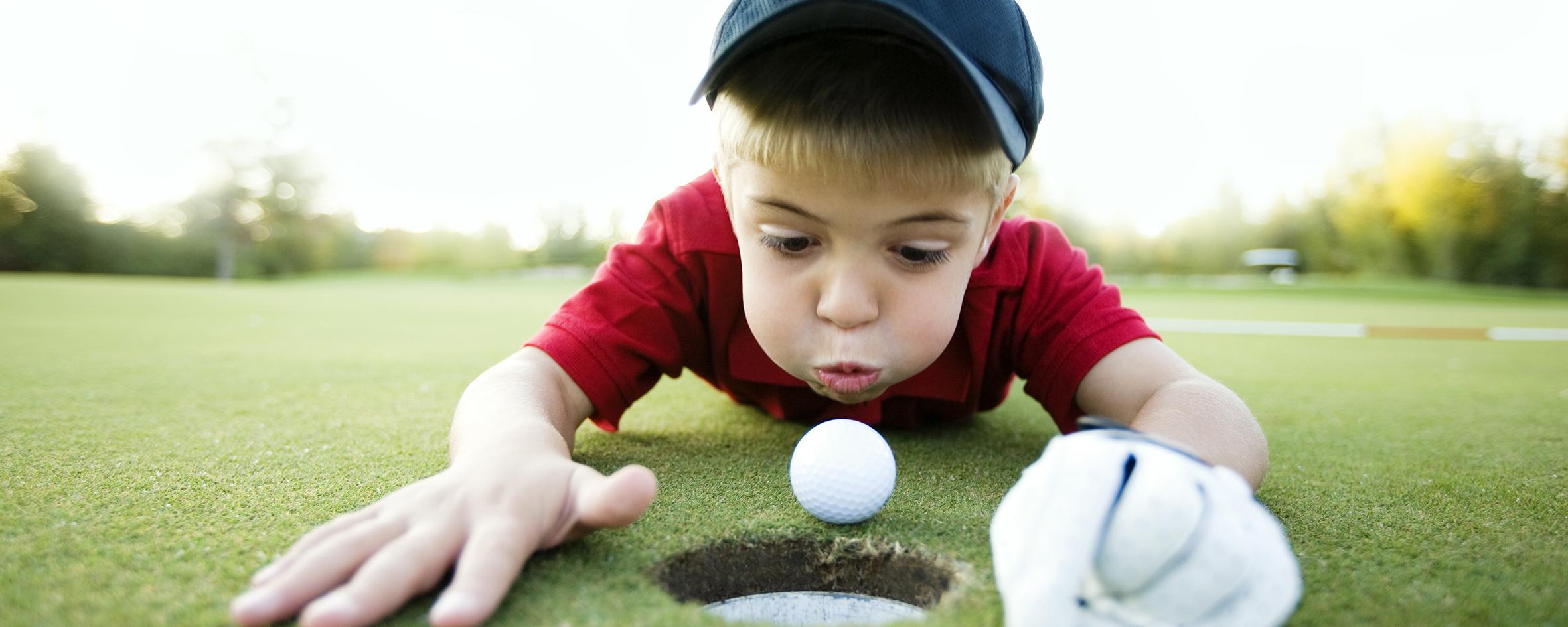 Pojke blåser ner golfboll i hål