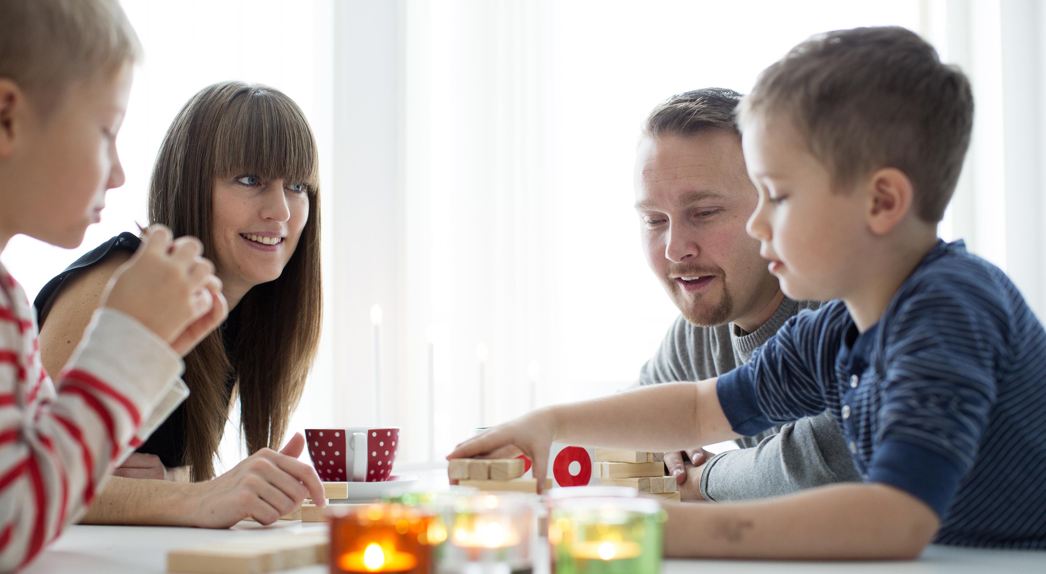 Barnfamilj spelar spel vid köksbordet