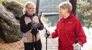 Två kvinnor går stavgång vid vatten