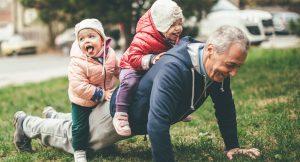 Man går armhävningar med två små barn på ryggen