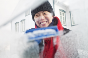 Kvinna skrapar is från vindruta.