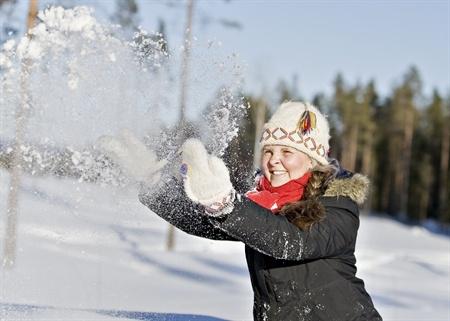 Barn som kastar snö i vinterlandskap.