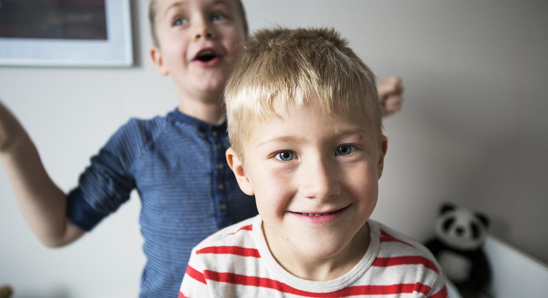 Två pojkar som busar med varandra. Den ena tittar rakt in i kameran och ler, den andra står snett bakom med armarna utslagna.