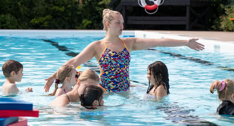 Simlärare håller simskola tillsammans med mindre barn.