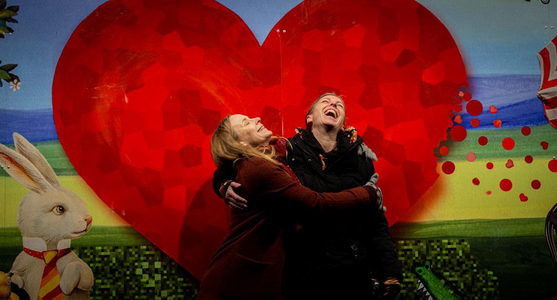 Två kvinnor håller om varandra och skrattar framför ett stort hjärta på väggen.