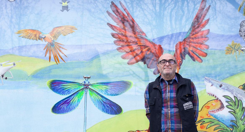 Man står framför en målad vägg med en papegoja