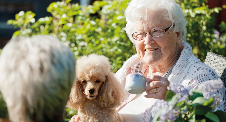 Äldre dam sitter utomhus med pudel i knät och en kaffekopp i handen.