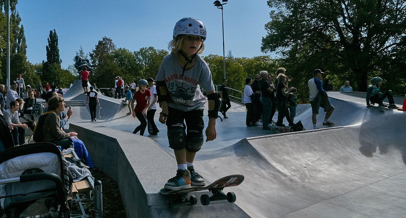 barn med hjälm står med skateboard
