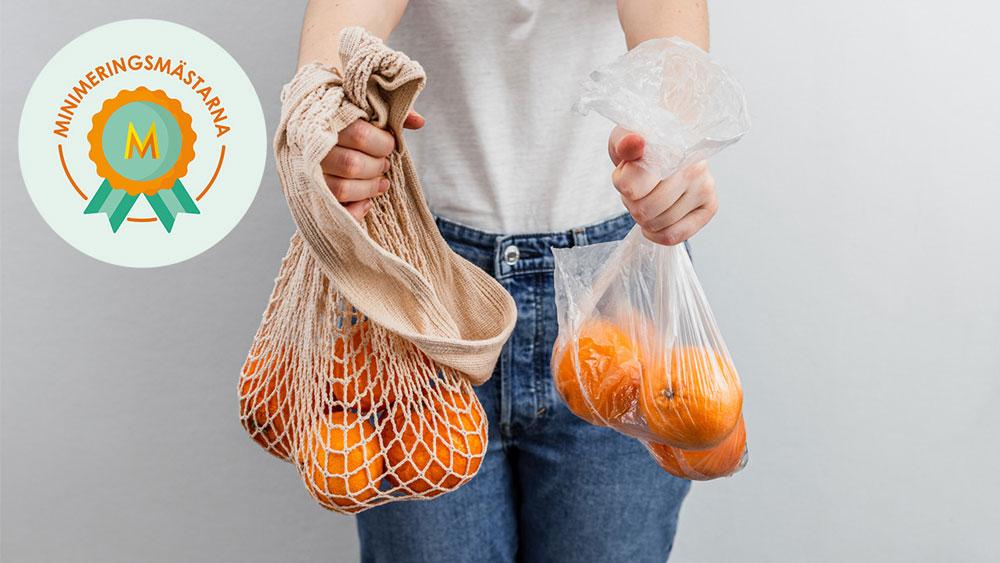 Person håller upp en tygpåse med apelsiner och en plastpåse med apelsiner